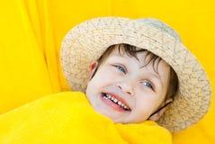 Un bambino sorridente nelle bugie di un cappello di paglia si è accoccolato in asciugamano giallo Fotografie Stock Libere da Diritti