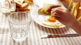Un bambino sta avendo prima colazione (uova rimescolate con pane tostato ed insalata) mentre un genitore versa il succo d'arancia archivi video
