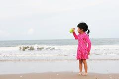 Un bambino sta giocando sulla spiaggia Fotografia Stock
