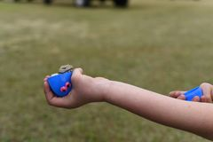 Un bambino sta giudicando un uovo di plastica blu farcito con soldi durante la caccia dell'uovo di Pasqua immagine stock