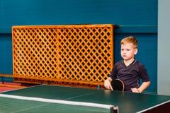 Un bambino sta vicino alla racchetta di tennis con le mani fotografia stock