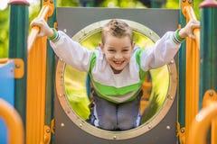 Un bambino sul campo da giuoco all'aperto Fotografie Stock