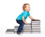 Un bambino sull'punti dei libri Fotografia Stock