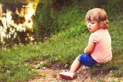 Un bambino sulla banca del lago Fotografia Stock Libera da Diritti