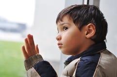 Un bambino sulla finestra Fotografia Stock