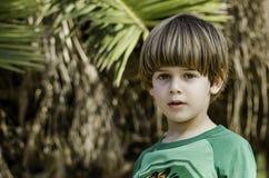 Un bambino sveglio con la priorità bassa degli alberi fotografia stock