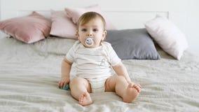 Un bambino sveglio e divertente si siede su un letto con una tettarella nella sua bocca e le palle in sua mano, il ragazzo guarda video d archivio