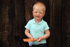 Un bambino sveglio gioca con un mestolo in una sabbiera Immagini Stock Libere da Diritti