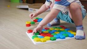 Un bambino sveglio raccoglie un'immagine dai grandi dei dettagli colorati multi Giocando con un puzzle stock footage