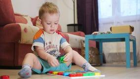 Un bambino sveglio raccoglie un'immagine dai grandi dei dettagli colorati multi Giocando con un puzzle video d archivio