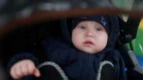 Un bambino in una carrozzina nell'ambito di una copertura trasparente archivi video