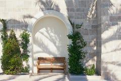 Un banc à la nuance d'un palmier Photo stock