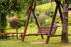 Un banc accrochant au jardin vert Photographie stock libre de droits