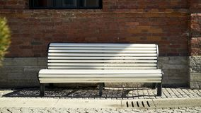 Un banc blanc vide dont une ombre tombe sur un paveme en pierre Images libres de droits