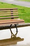 Un banc et une réflexion en parc après la pluie Image libre de droits