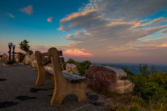 Un banc solitaire et les jumelles de visionnement regarde au-dessus de la montagne le coucher du soleil Image libre de droits