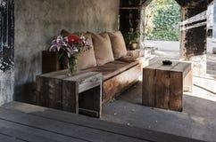 Un banco all'aperto accogliente con i cuscini e una tavola immagine stock