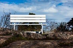 Un banco bianco in natura su una collina rocciosa Fotografia Stock