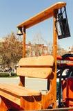 Un banco de madera con una campana y una linterna en un coche de bomberos rojo foto de archivo