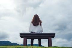 Un banco de madera en el parque con el fondo nublado y melancólico del cielo imagenes de archivo