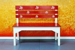 Un banco de madera rojo precioso en el parque de la ciudad foto de archivo libre de regalías