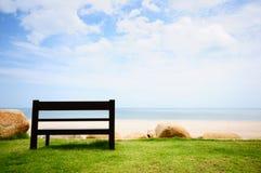 Un banco di legno vicino ad una spiaggia di sabbia bianca che guarda all'oceano fotografie stock libere da diritti
