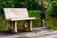 Un banco di pietra isolato vicino ad uno stagno nel giardino Immagini Stock