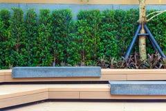 Un banco di pietra moderno sotto l'albero nel giardino Fotografia Stock