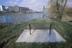 Un banco que pasa por alto un parque industrial en el río del colorete en Detroit, Michigan Imagenes de archivo