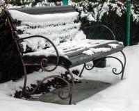 Un banco sitiado por la nieve está en un jardín Foto de archivo