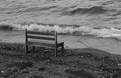 Un banco vacío en la playa a través de ondas Fotos de archivo