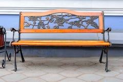 Un banco vuoto del ferro battuto con gli accenti di legno contro le pareti blu Fotografia Stock Libera da Diritti