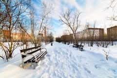 Un banco vuoto nel parco innevato della città Immagine Stock
