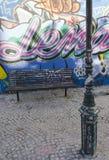 Un banco y un polo ligero en Calcado hacen la calle de Lavra en Lisboa Fotografía de archivo libre de regalías