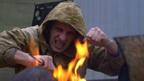 Un bandido tira de un cuchillo cerca del fuego almacen de metraje de vídeo