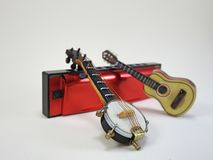 Un banjo miniatura y una guitarra acústica miniatura apoyados para arriba en una armónica roja foto de archivo