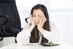 Un bankrupt, se rompió y la mujer frustrada está teniendo problemas financieros con las monedas dejadas en la tabla y una cartera imagen de archivo