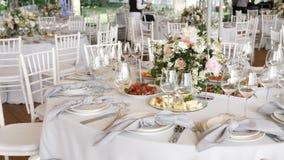 Un banquet avec de grandes tables avec les nappes blanches a assorti les plats délicieux, compositions florales avec des bougies  banque de vidéos