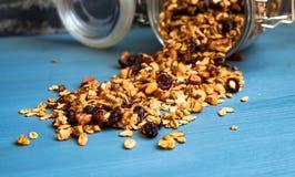 Un barattolo dei muesli sparsi su un fondo blu, primo piano, muesli, cereali per sano immagine stock