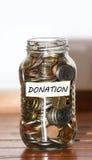 Un barattolo di vetro in pieno del concetto delle monete per le donazioni Immagini Stock Libere da Diritti