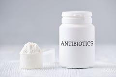 Un barattolo e un cucchiaio con la polvere degli antibiotici su gray Immagini Stock