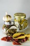 Un barattolo quadrato con il barattolo della foglia e del pepe di alloro ed il peperoncino rosso e l'aglio Fotografia Stock