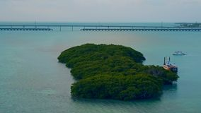 Un barco anclado por una pequeña isla en la salida del sol metrajes