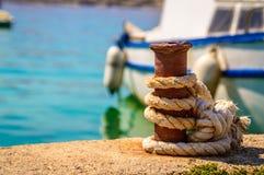 Un barco atado a un embarcadero en día de verano brillante con el mar o el ocea azul Fotografía de archivo libre de regalías