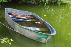 Un barco azul cielo, mitad-hundido viejo de la fibra de vidrio en una charca alga-verde en un parque tailandés del jardín fotos de archivo libres de regalías