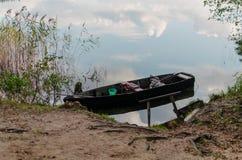 Un barco cerca de un banco del lago Foto de archivo libre de regalías