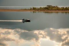 Un barco con un hombre que flota en el agua entre la reflexión de nubes Fotografía de archivo
