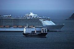 Un barco de cruceros en comparación con un buque mercante Golfo del spezia del la Italia imagenes de archivo