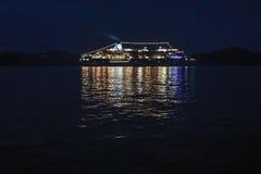 Un barco de cruceros que navega abajo de la costa noruega en la noche, brillando Fotos de archivo