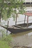 Un barco de madera con un tejado hundido en el lado del carril del río debajo del árbol foto de archivo libre de regalías